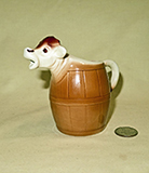 Goebel cow head sticking out of a barrel cow creamer