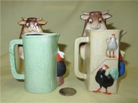 Two multicolored S&V pitchers of cow caricature being milked, front