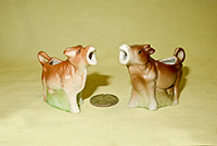 Two small German cow creamers on bases