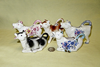 5 small Japanese standing and lying cow creamers