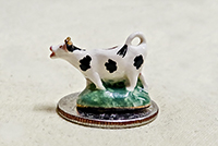 Miniature holstein creamer on green base