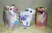 Two purplish and one white and blue cow caricature creamers
