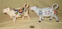 Two differently decorated French cow creamers from similar molds