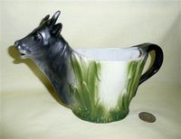 Cup-like cow creamer with black head and tail