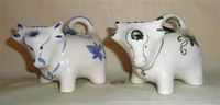 Two Welsh cow creamers with pour holes on their foreheads
