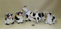 Five black and white cow creamers