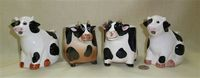 Two pairs of black & white cow creamers from different manufacturers