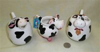 Three bulbous-nosed round black and white cow caricature creamers