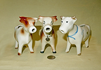 Three similar cow creamers in popular form