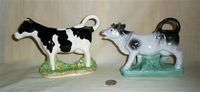 Jamess Herriot black and white cow creamer, and one on a base with a stand under the belly