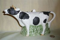 Large black and white cow creamer filled below with gress