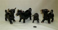 Four red clay Japanese black cow creamers with gold horns