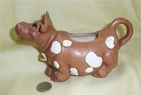 Brown cow caricature creamer with white spots