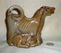 Guernsey Pottery brown cow creamer with kneeling milkmaid, right