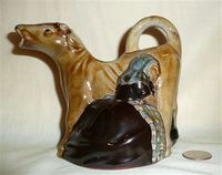 Guernsey Pottery brown cow creamer with kneeling milkmaid, left