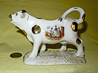 Cow creamer on base with picture of 'Welsh Costumes' on left