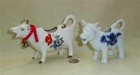 Two white cow creamers with flowers
