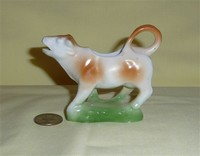 Small light brown and white cow creamer on green base