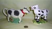 Two cow creamers on stands