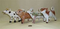 Four striding cow creamers