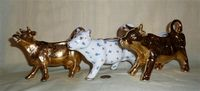 Two gold plated cow creamers and a white one with small flowers