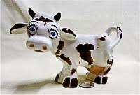 Forlorn black and white cow creamer with blue eyes