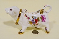 Smnall French pporcelain cow creamer witth flowers and gold trim, side