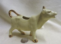 older cream colored cow creamer with gold trip