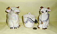 Two white sitting up bull creamers and sugar bucket