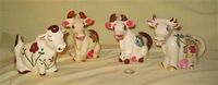 Four similar sitting up cow caricature creamers