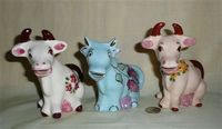 Three similar sitting up cow caricature creamers