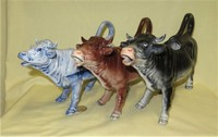 Three German realistic porcelain cow creamers from similar nolds with different coloration
