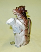 Brown German cow creamer with removable head, standing holding a pitcher