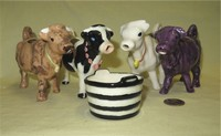 Four paint-it-yourself cow creamers with bells, and a sugar bucket