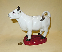 White Maitland-Smith cow creamer on red base