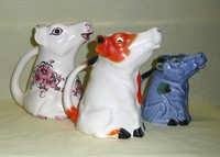 Three pointy nosed flat headed sitting up cow creamers