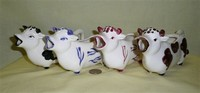 Four similar long low cow caricature creamers from Japan