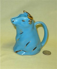 Blue sitting up cow creamer with single opening on flat top of head