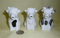Three similar small white sitting cow cramers from Dansk, Spain and UK