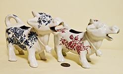 two large mouthed smiling white flowered English cow creamers