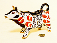 Lustre splotted orange and black on white cow creamer