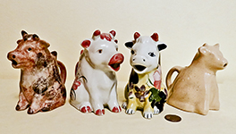 Four similar sitting up cow creamers from different countries