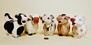 Five similar rotund cow caricature creamers from all over