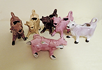 six Kenmar-style cow creamers in various colors