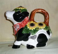 Sitting cow pitcher with daisys
