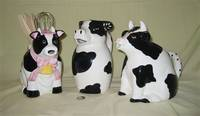3 large black and white cow pitchers