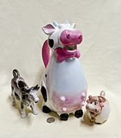 Three cow creamers of different sizes