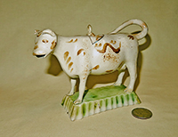 Small white cow creamer with brown marks