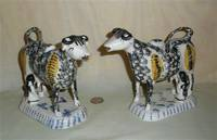 Matrched pair of black and yellow sponged Prattware cow creamers with armless milkmaids