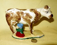 White and brown cow creamer with milkmaid